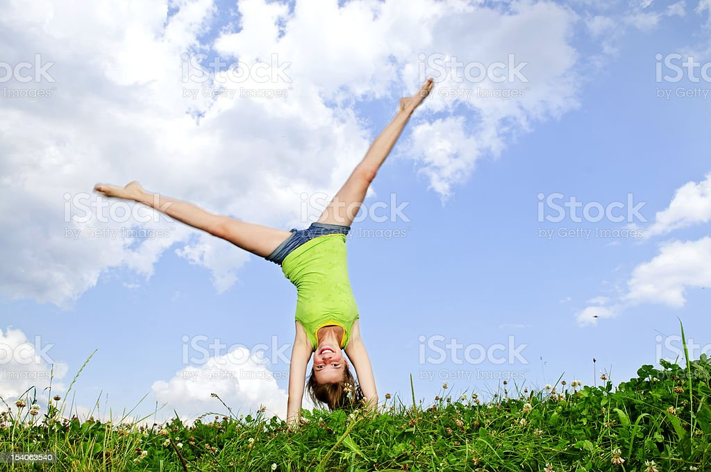 Young girl doing cartwheel stock photo