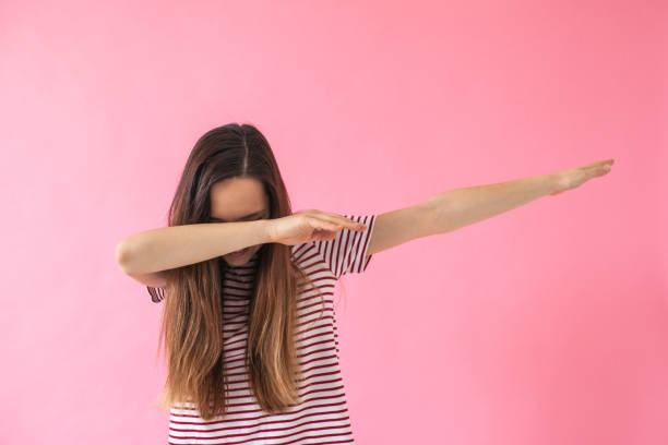 Young girl doing dab dance gesture. stock photo