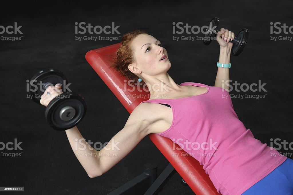 Chica joven haciendo pesa Incline Levantamiento de pesas en banco de ejercicios - Foto de stock de Ejercicio físico libre de derechos