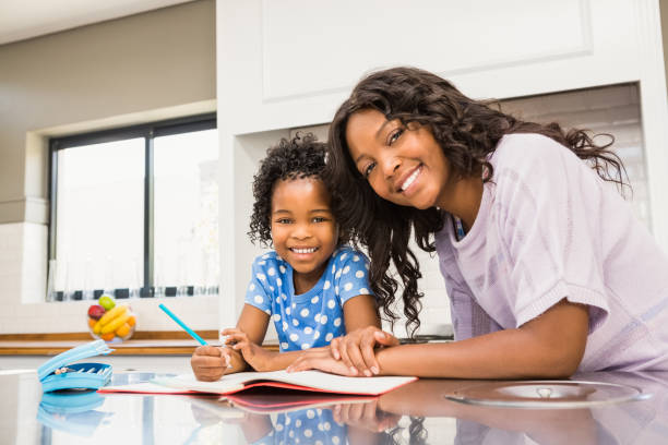 Young girl doing her homework with her mother stock photo