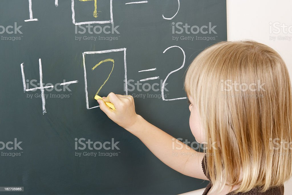 Young girl doing mathematical problems on the blackboard stock photo