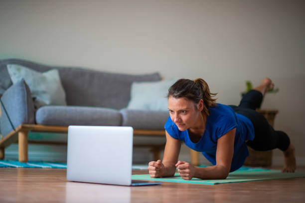 Young girl doing online exercise session at home doing a plank selective focus stock photo