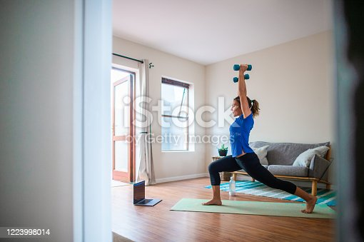 Side view of a Young Caucasian girl doing online exercise session at home on her laptop mobile device.  She is in a living room at home during lockdown.  She is looking at the device screen following instruction presenting a class.  She is doing strengthening exercises with dumbbells.