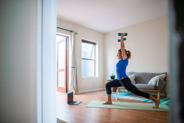 Young girl doing online exercise session at home with dumbbells stock photo