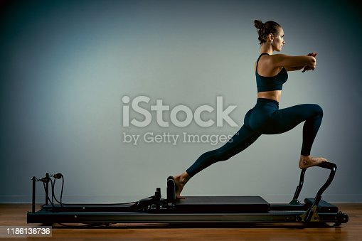 istock Young girl doing pilates exercises with a reformer bed. Beautiful slim fitness trainer on a reformer gray background, low key, art light, copy space advertising banner 1186136736