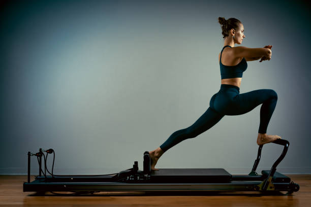 Young girl doing pilates exercises with a reformer bed. Beautiful slim fitness trainer on a reformer gray background, low key, art light, copy space advertising banner stock photo