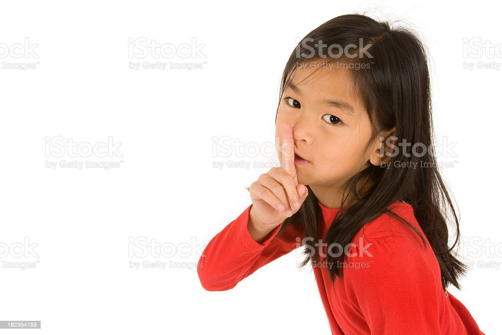 Young girl doing the be quiet sign with her hand stock photo