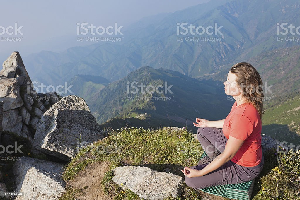 Young girl doing yoga on top. stock photo