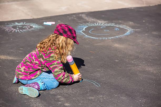 junges mädchen zeichnen mit kreide auf der auffahrt - camouflagekleidung mädchen stock-fotos und bilder
