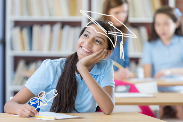 Young girl dreams about her future Cute middle school student thinks about her future. She is smiling with her hand on her chin. cute middle school girls stock pictures, royalty-free photos & images