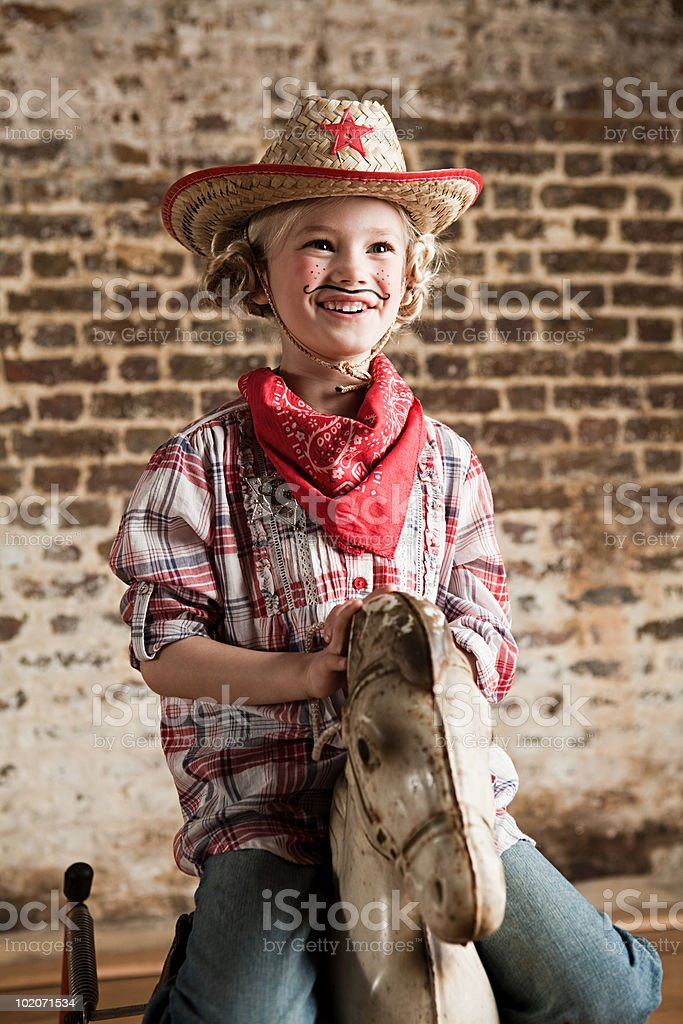 Young girl dressed as cowgirl with rocking horse stock photo