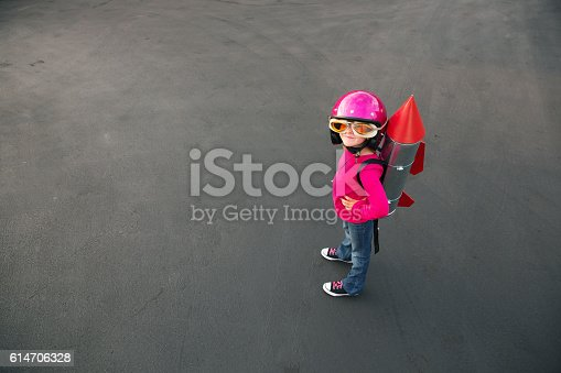 A young girl standing on a road, wearing jeans, a red shirt, and black shoes. She is equipped with oversized goggles and a large pink helmet.  He has a homemade rocket strapped to her back, with a silver body and red fins and top.  The girl is looking at the camera