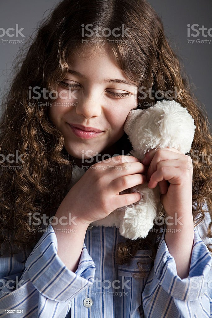 Young girl dressed in pyjamas holding teddy bear royalty-free stock photo