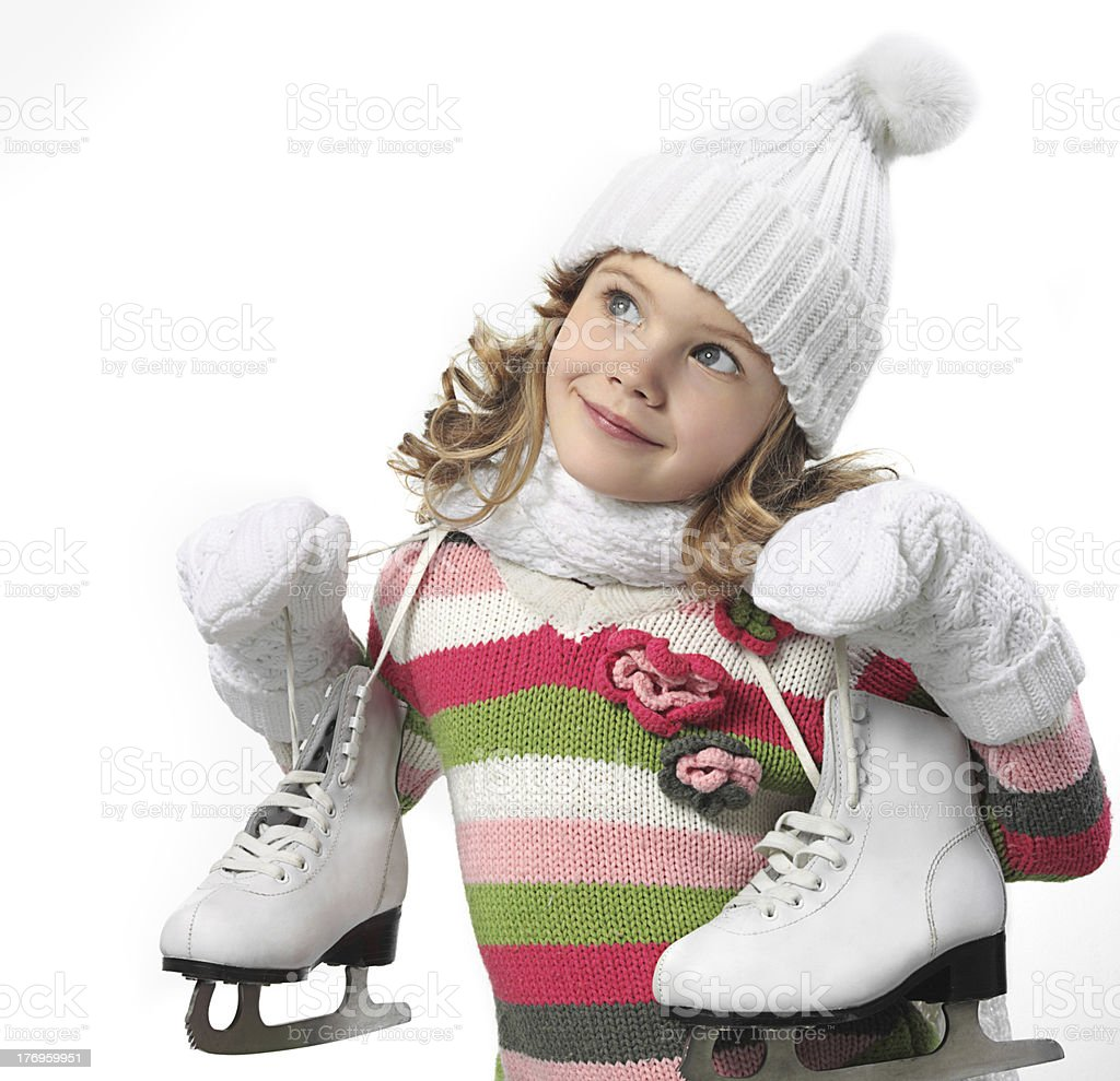Young girl dressed in winter clothes and holding ice skates royalty-free stock photo