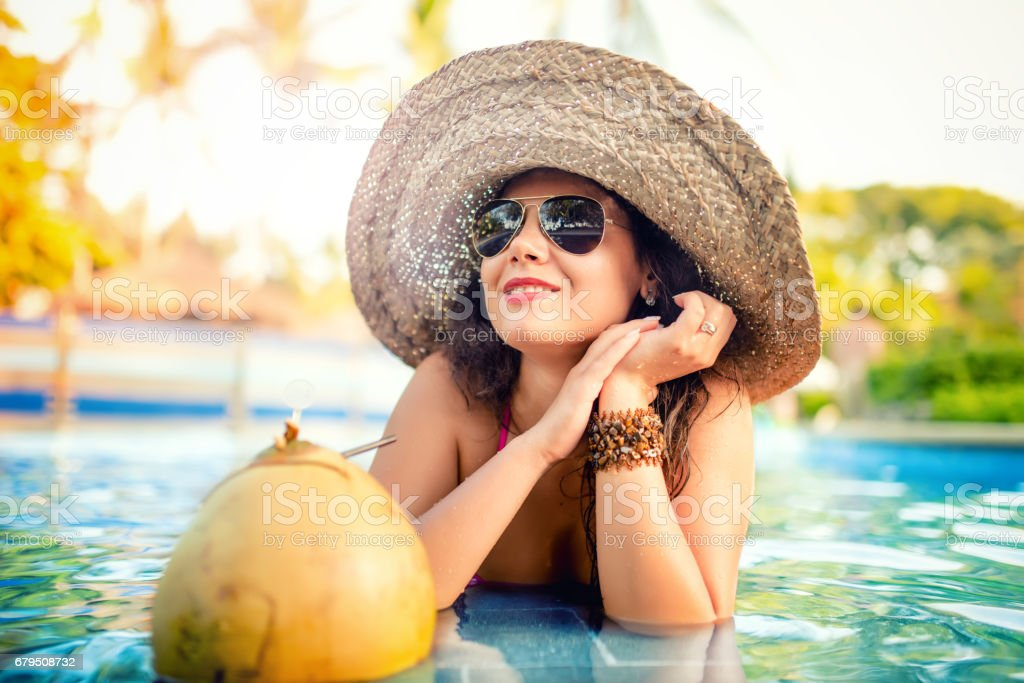 Young girl drinking coconut cocktail, attractive and sexy young woman having refreshment drink in pool'n royalty-free stock photo