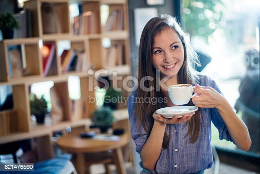 694187664 istock photo Young girl drinking coffee in cafe 621476590