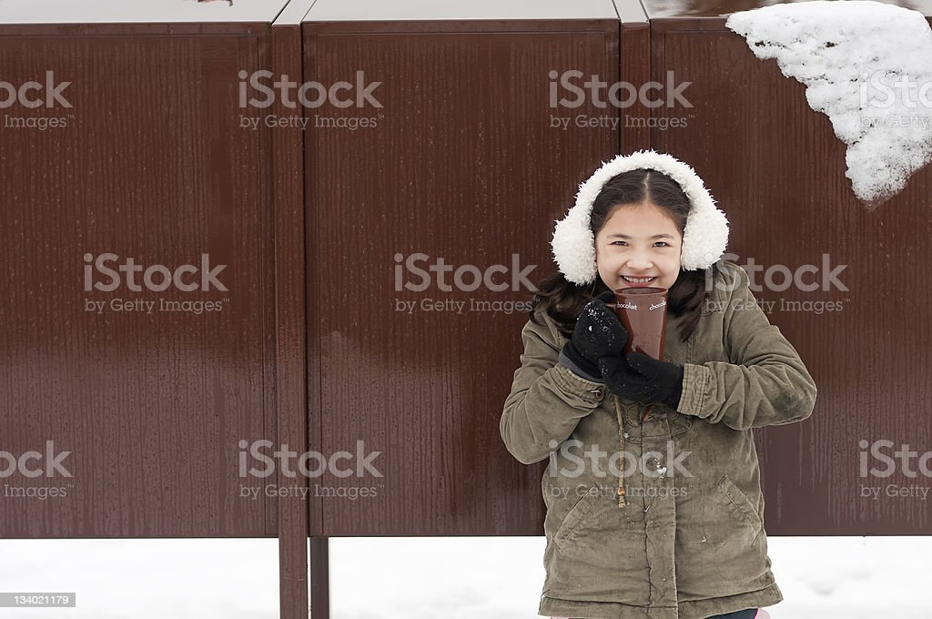 Young Girl Drinking Hot Chocolate on Snowy Day royalty-free stock photo