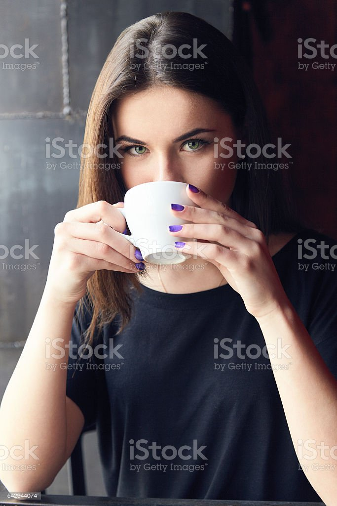 Young girl drinking tea in cafe and holding cup stock photo