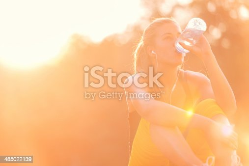 Young girl drinking water after workout in nature