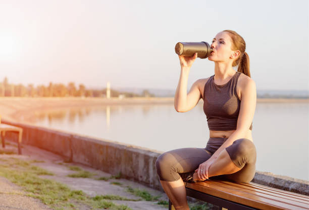young girl drinks a protein cocktail from a schweeter after jogging stock photo