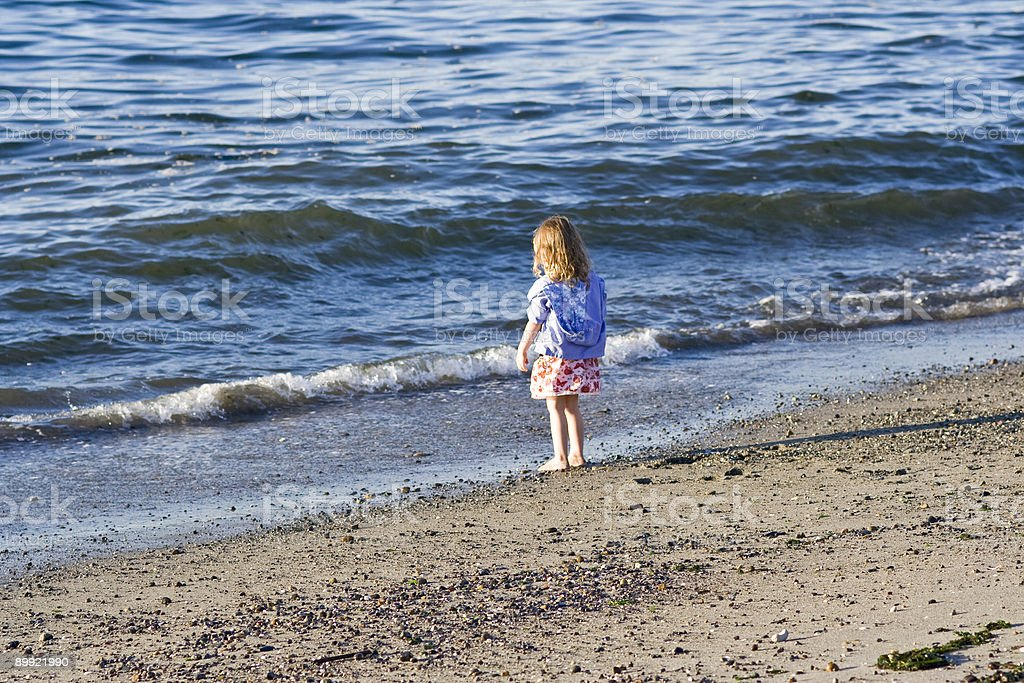 Young girl during sunset stares at waves on beach royalty-free stock photo