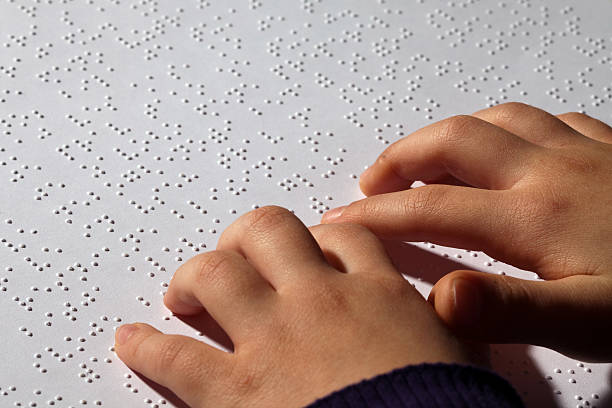 Young girl eading braille stock photo