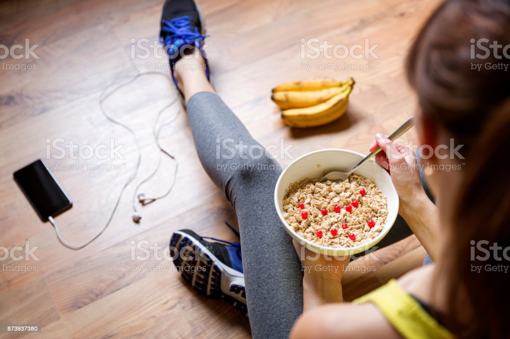Young girl eating a oatmeal with berries after a workout . Fitness and healthy lifestyle concept. royalty-free stock photo