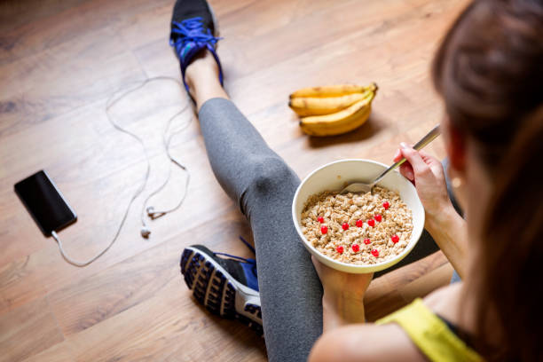 Young girl eating a oatmeal with berries after a workout . Fitness and healthy lifestyle concept. stock photo