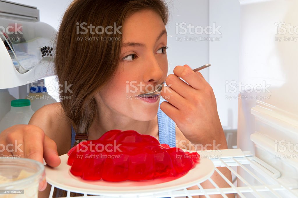 Young Girl Eating Jelly from Fridge royalty-free stock photo