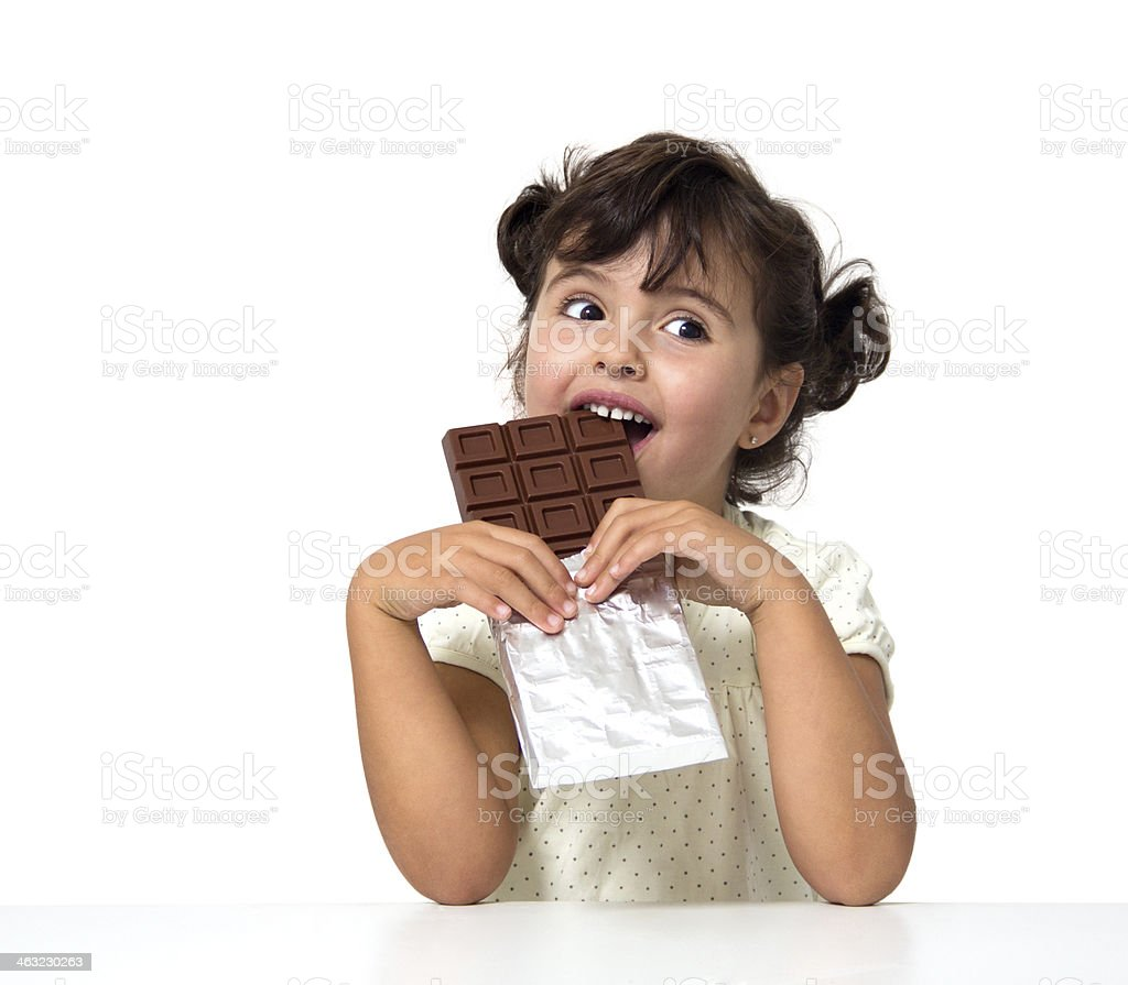 Young girl eating large chocolate bar stock photo