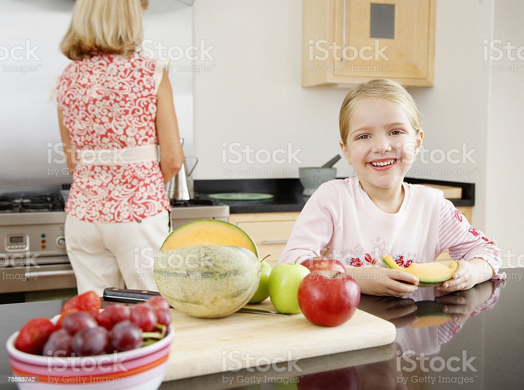 A young girl eating melon while her grandmother tidies royalty-free stock photo