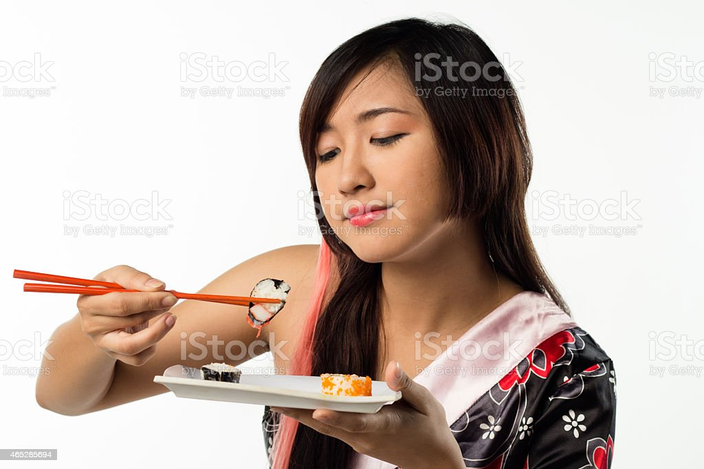 young girl eating sushi stock photo