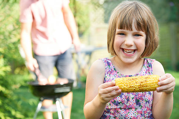 Young Girl Eating Sweetcorn At Family Barbeque stock photo