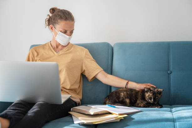 young girl employee in mask with laptop computer in self isolation working from home, coronavirus quarantine. remote working of business worker, online education. - covid testing zdjęcia i obrazy z banku zdjęć