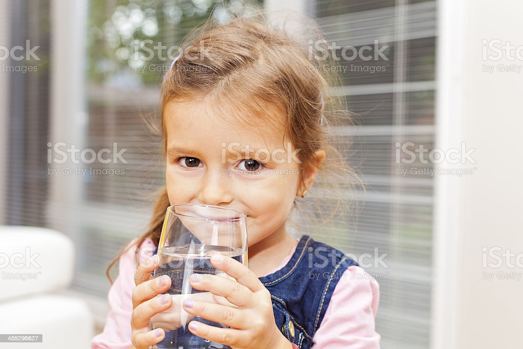 A young girl enjoying a glass of water stock photo