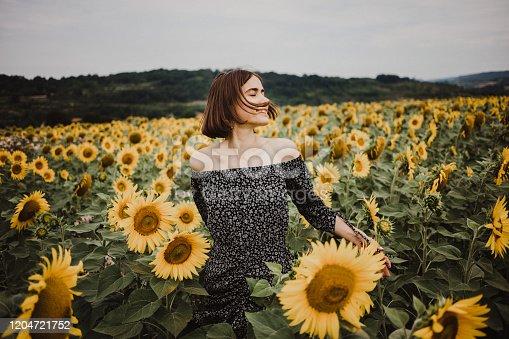 Beautiful girl in field of sunflowers