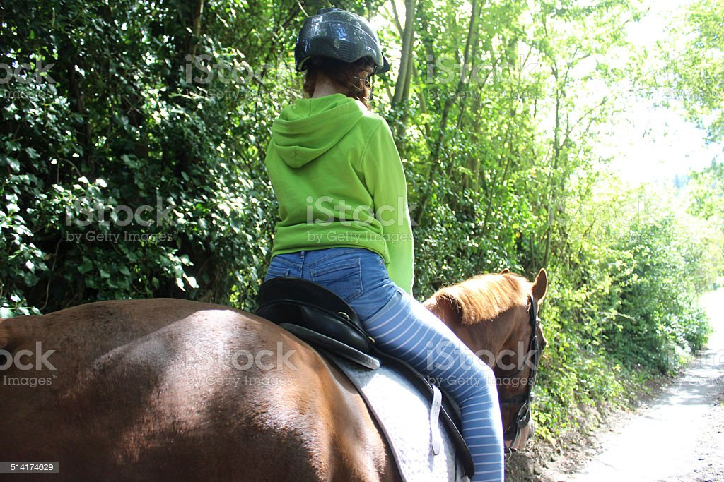 Young girl enjoying horse riding lesson, wearing equestrian helmet hat stock photo