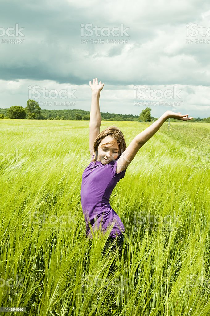 Young girl enjoying nature in a wheat field. royalty-free stock photo