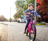 Young Girl Enjoying Riding Bicycle in a City.