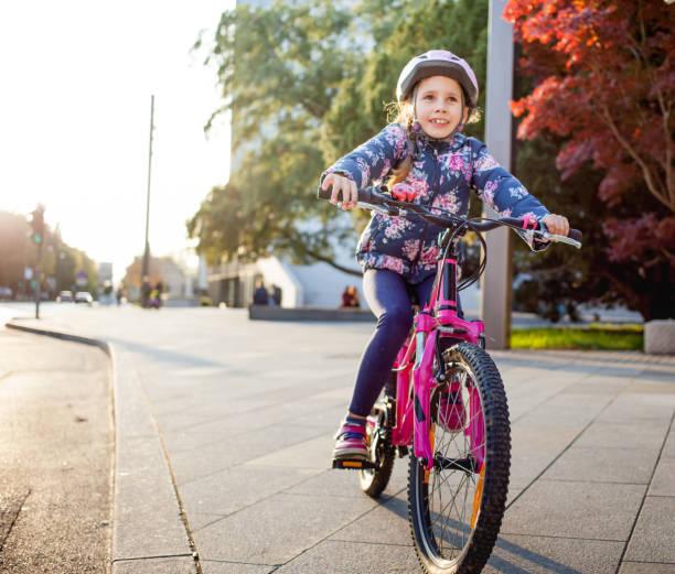 junge mädchen genießen, radfahren in der stadt - kinderfahrrad stock-fotos und bilder