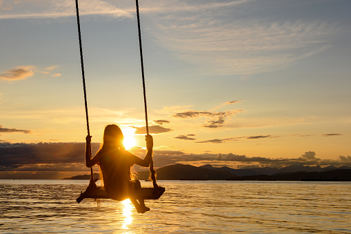 Girl swinging at sunset with incredible views over the sea. Young girl enjoying summer vacation.
