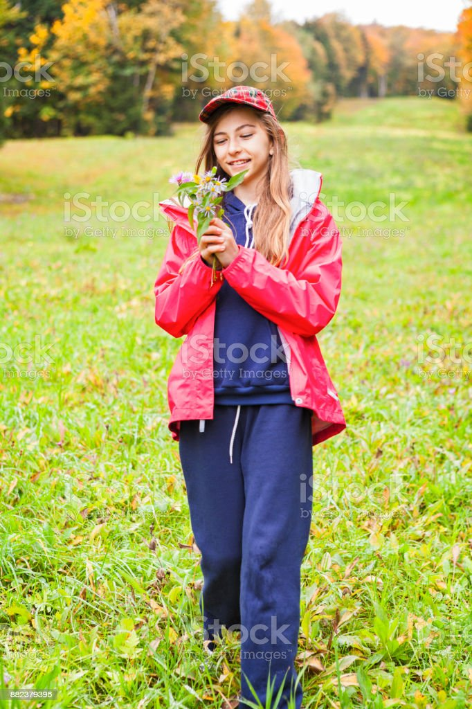Young girl enjoying wildflowers on an autumn day stock photo