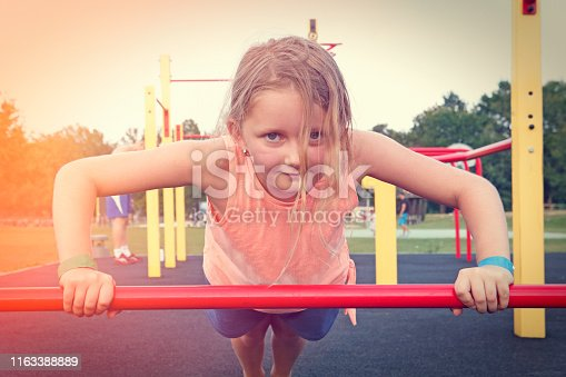 Young sporty girl exercising push-ups at outdoor playground