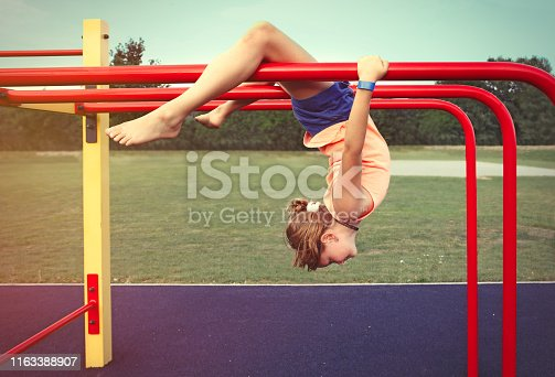 Young sporty girl exercising at trapeze bar