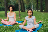 istock Young girl exercising youga with her mother in the park 1023553140