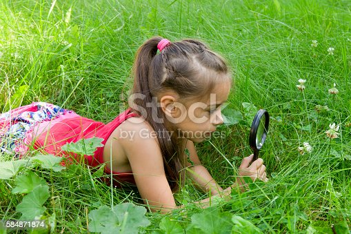 istock Young girl exploring nature looking at magnifying glass 584871874