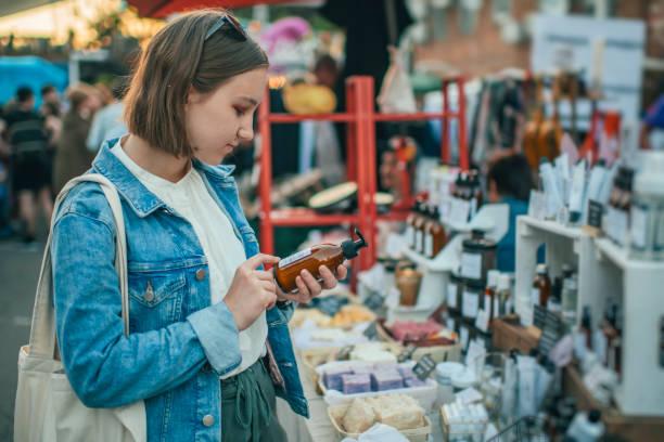 Junges Mädchen erkundet Bio-Körperpflegeprodukte auf einem Open-Air-Markt mit Null-Abfall-Konzept – Foto