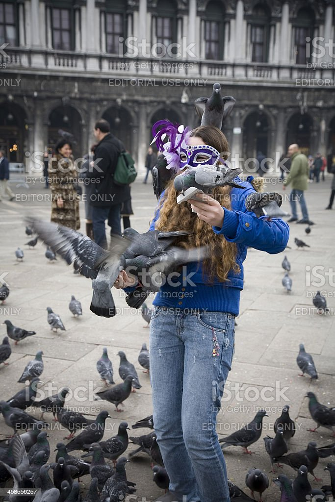 Young girl feeding pidgeons on St Marks square. royalty-free stock photo
