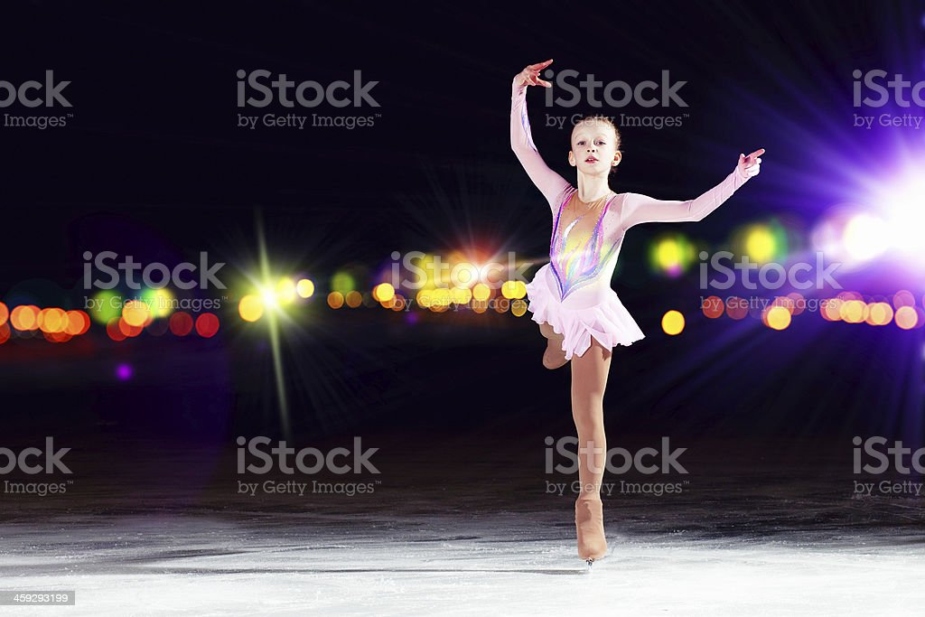 Young girl figure skating on ice with blurred lights in back stock photo
