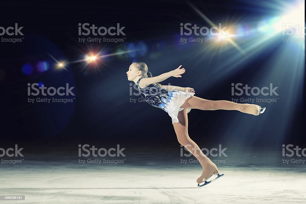 Young girl figure skating with spotlight on her stock photo